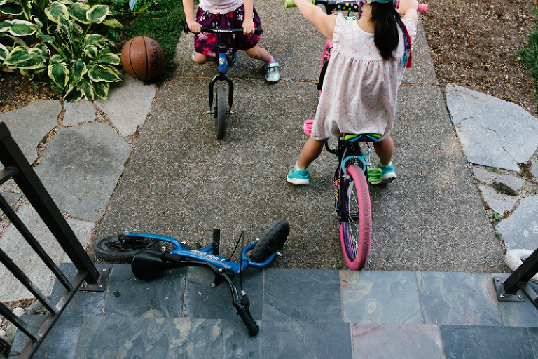 girls on bikes at front steps - documentary family photography